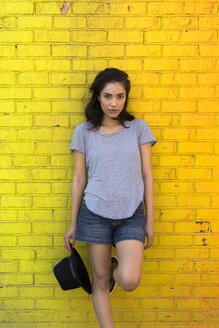 Young woman leaning against yellow brick wall - GIOF000175