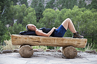 USA, New Mexico, woman relaxing on bench - NNF000246