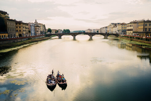 Italy, Florence, boats on Arno river at sunset with St Trinity Bridge in the background - GEM000445