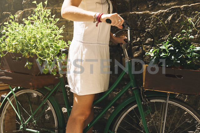 Woman on a bicycle carrying plants - GEMF000454