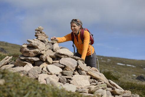 Italy, Alto Adige, Urtijei, hiker putting stone on a heap of stones - LBF001234