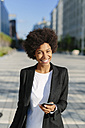 USA, New York City, portrait of smiling businesswoman with smartphone - GIOF000193