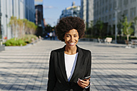 USA, New York City, portrait of smiling businesswoman with smartphone - GIOF000196