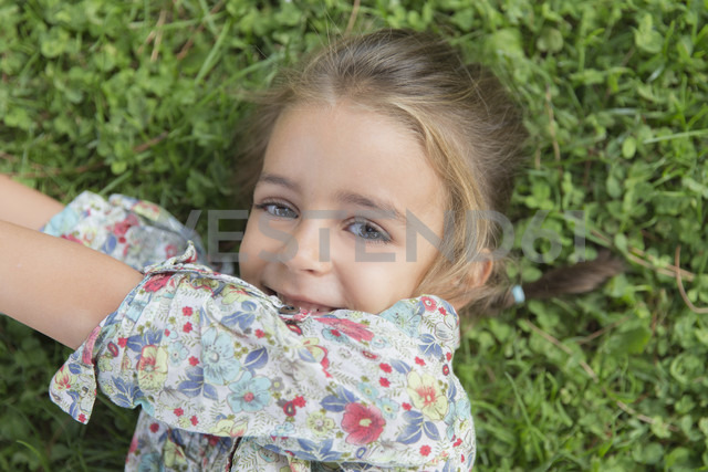 Portrait of smiling little girl lying on a meadow - ERLF000055