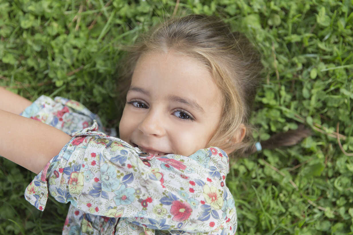 Portrait of smiling little girl lying on a meadow - ERLF000055 - Enrique Ramos/Westend61