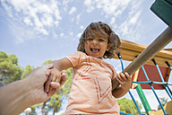 Portrait of smiling little girl on a playground being held by her father's hand - ERLF000058