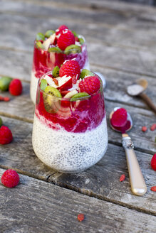 Two glasses of chia pudding with cocos, raspberry sauce and several fruits - SARF002169
