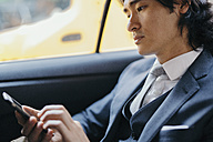 Businessman on back seat of car using cell phone - GIOF000213