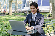 USA, New York City, Manhattan, businessman working with a laptop in Bryant Park - GIOF000216
