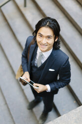 Smiling businessman standing on stairs holding digital tablet - GIOF000222