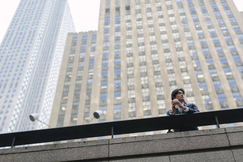 USA, New York City, businessman in front of skyscrapers in Manhattan - GIOF000225