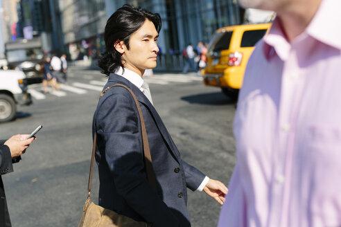 USA, New York City, businessman crossing the road in Manhattan - GIO000228