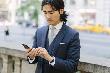 USA, New York City, businessman looking at cell phone in Manhattan - GIOF000237