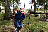 Two little children playing with swing in a garden - MGOF000809