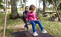 Two little children playing with swing in a garden - MGOF000812