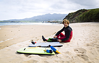 Spain, Asturias, Colunga, body board rider preparing on the beach - MGOF000824