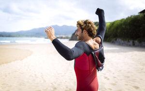 Spain, Asturias, Colunga, surfer preparing on the beach - MGOF000830