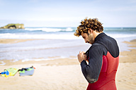 Spain, Asturias, Colunga, surfer preparing on the beach - MGOF000836