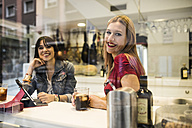 Two happy young women in a bar with drinks and digital tablet - JASF000135