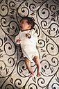 Yawning newborn baby boy lying on the couch - JASF000141