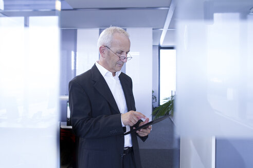 Businessman in open space office using digital tablet - SGF001919