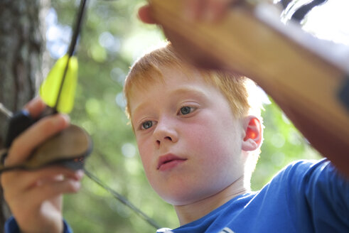 Portrait of a boy with a bow in an adventure park - JEDF000250
