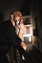 Bald man smoking on balcony at night - JASF000144