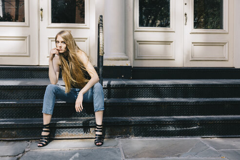 USA, New York City, pensive young woman sitting on stairs in front of an entry door - GIOF000257