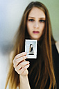 Young woman holding a polaroid of herself - GIOF000269