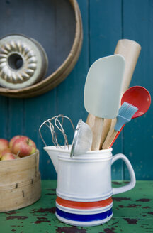 Baking utensils in pitcher, cake pans on wall - GISF000170