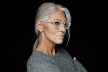 Portrait of woman with grey hair wearing glasses in front of black background - CHAF001487
