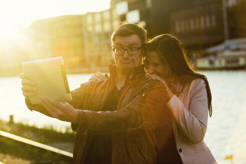 Germany, Muenster, couple taking a selfie with digital tablet at the harbour at backlight - TAM000270