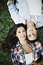 Portrait of young couple in love lying head to head on a meadow - JRFF000107