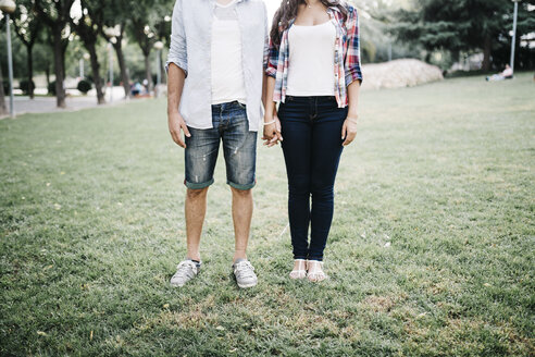 Young couple in love standing on a meadow in a park holding hands - JRFF000113
