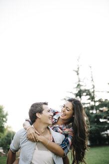 Young man giving his girlfriend a piggy back on a meadow in a park - JRFF000125
