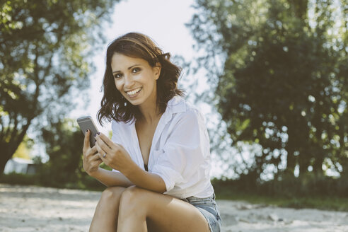 Portrait of smiling woman with smartphone sitting on the beach - MFF002249