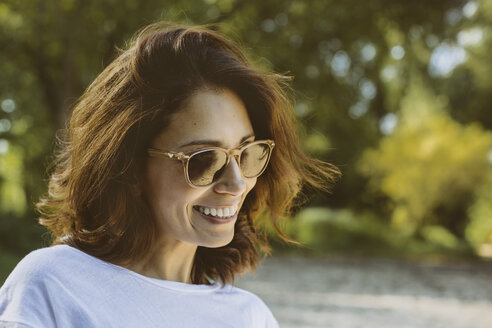Portrait of smiling woman with brown hair wearing sunglasses - MFF002255