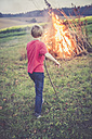 Back view of a boy watching camp fire on a meadow - SARF002196