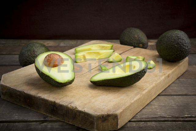 Whole and sliced avocado on wooden board - LVF003979
