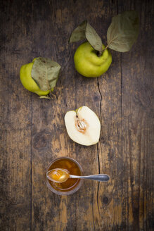 Whole and sliced quinces and a glass of quince jam on wood - LVF003981