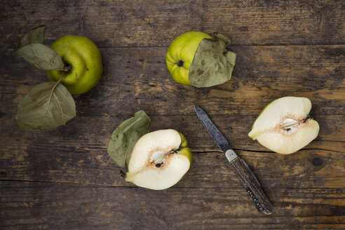 Whole and sliced quinces and a pocket knife on wood - LVF003984