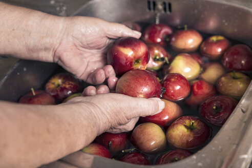 Senior woman cleaning apples in a sink, close-up - MIDF000686