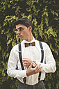 Portrait of elegant young man wearing wrist watch and a wooden bow tie - RAEF000534