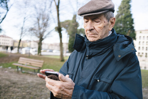 Portrait of senior man with smartphone in a park - GIOF000274