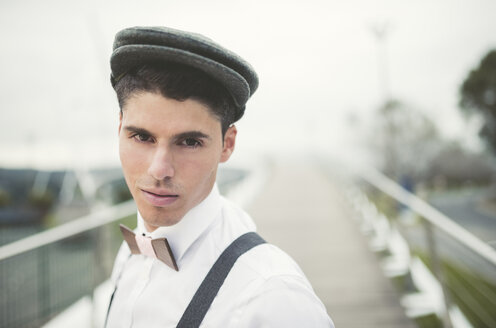 Portrait of young man wearing beret and a wooden bow tie - RAEF000538