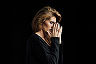 Portrait of woman with closed eyes and hands on her face in front of black background - CHAF001514