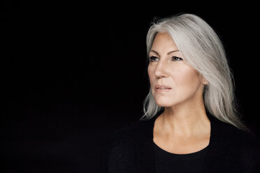 Portrait of mature woman with grey hair in front of black background - CHAF001517
