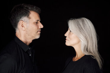 Portrait of mature man and mature woman wearing black clothes in front of black background - CHAF001532