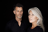 Portrait of mature man and mature woman wearing black clothes in front of black background - CHAF001535