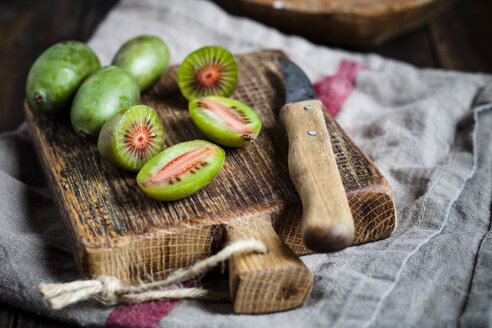 Sliced and whole mini kiwis and a kitchen knife on wooden chopping board - SBDF002302